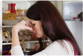 Woman pinching her nose because of rotten food